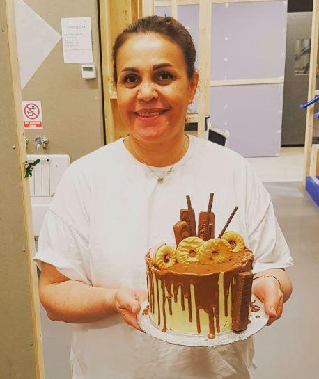 Very happy student holding her chocolate drip cake