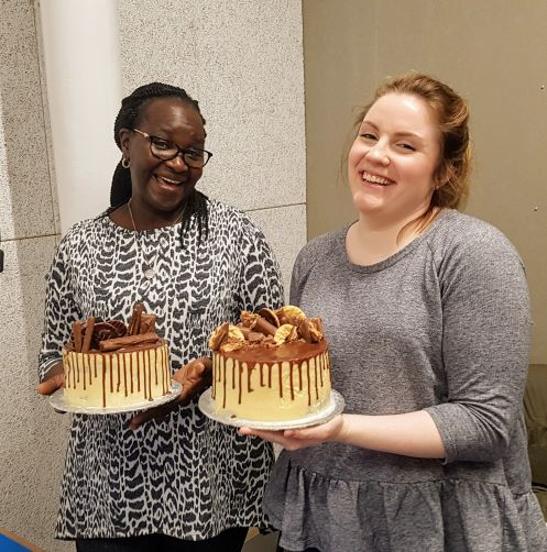 Two very happy students holding their chocolate drip cakes
