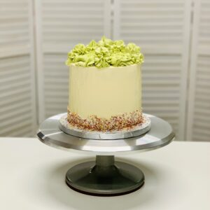 a cake decorated in buttercream and sprinkles with green frosting on top